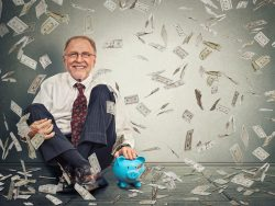 Excited happy senior business man sitting on a floor with piggy bank under a money rain isolated on gray wall background.