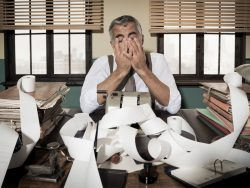 Desperate accountant head in hands surrounded by bills on paper tape, 1950s style office