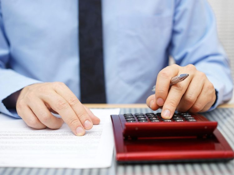 Businessman calculating and checking articles of agreemen
