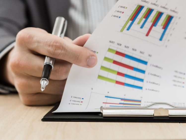 Businessman hand showing financial report on table