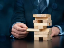 Businessman remove one piece from jenga tower Risk management concept metaphor