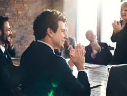Corporate Business Team clapping success at Boardroom meeting