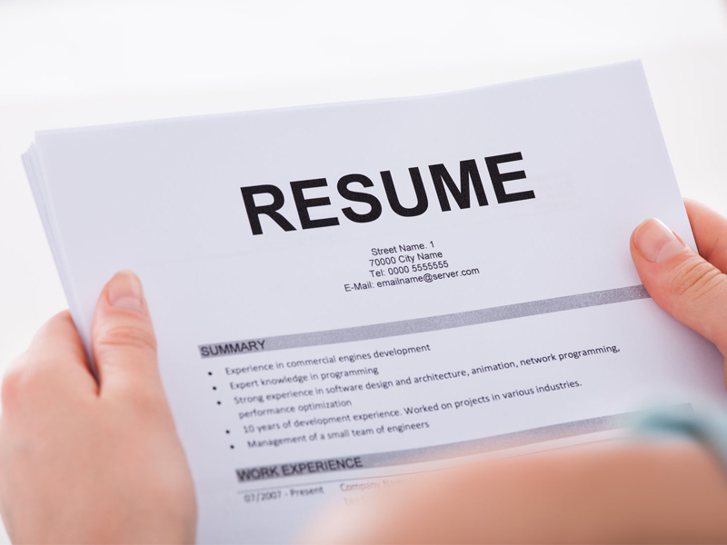 Cropped image of young woman holding resume over white