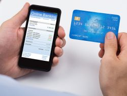 Close-up Of Person With Credit Card And Mobile Phone Doing Online Banking