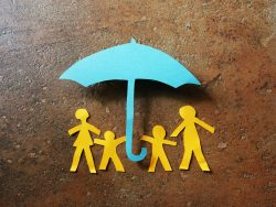 Paper family of four under a paper cutout insurance umbrella