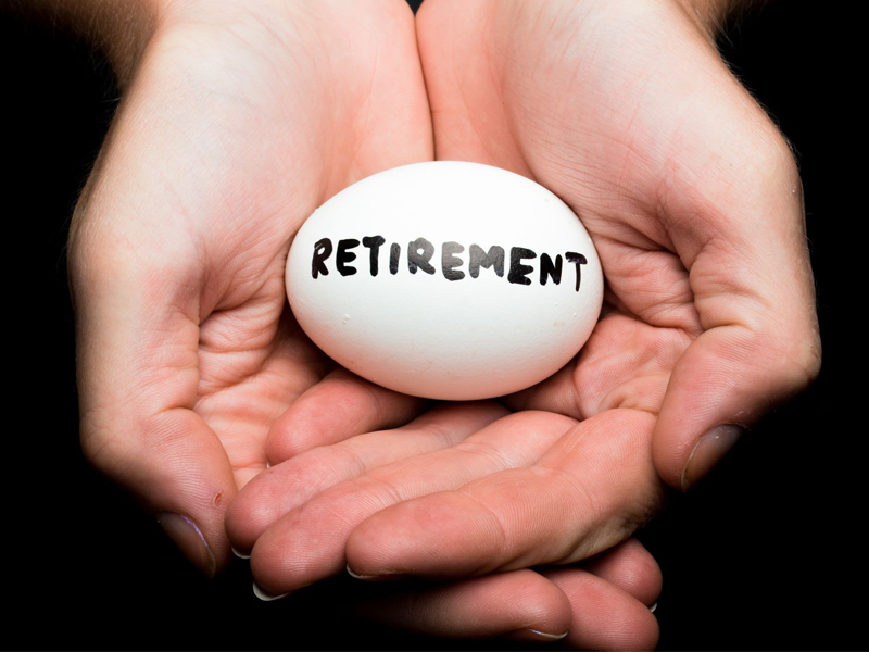 Retirement written on egg in hands, nest egg, savings