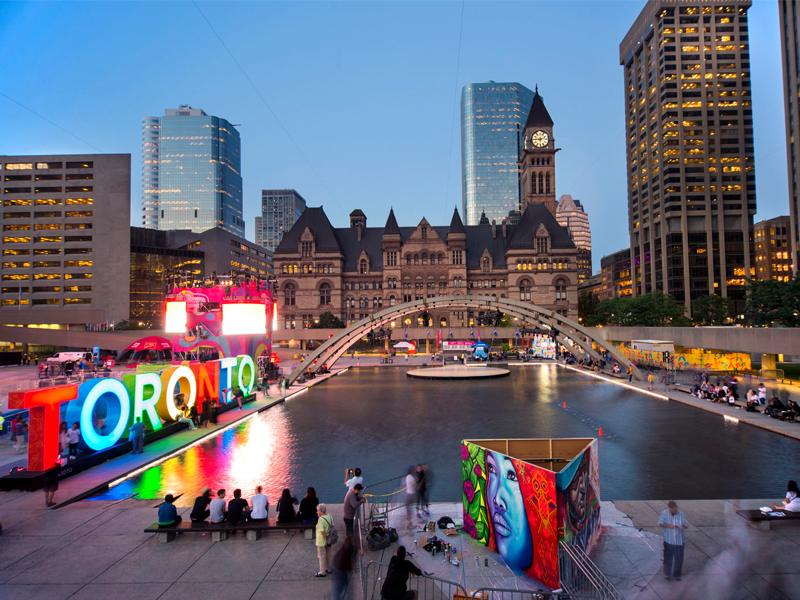 Toronto sign in Nathan Phillips Square with Old City Hall and downtown buildings in the back