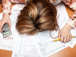 Woman face down on desk, overwhelmed by debt and calculations with calculator