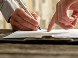 businessman showing where to sign agreement law contract pen