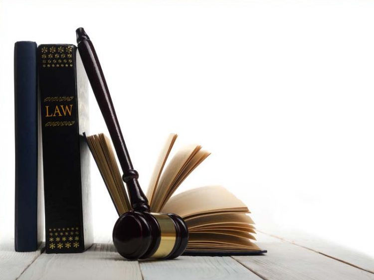 Open law book with a wooden judges gavel on table in a courtroom or law enforcement office isolated on white background