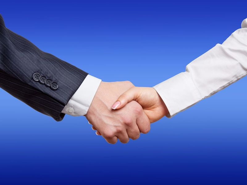 man woman handshake by close up on a blue background