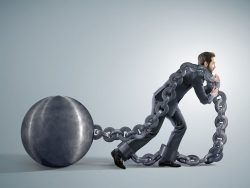 xhausted businessman dragging heavy chains