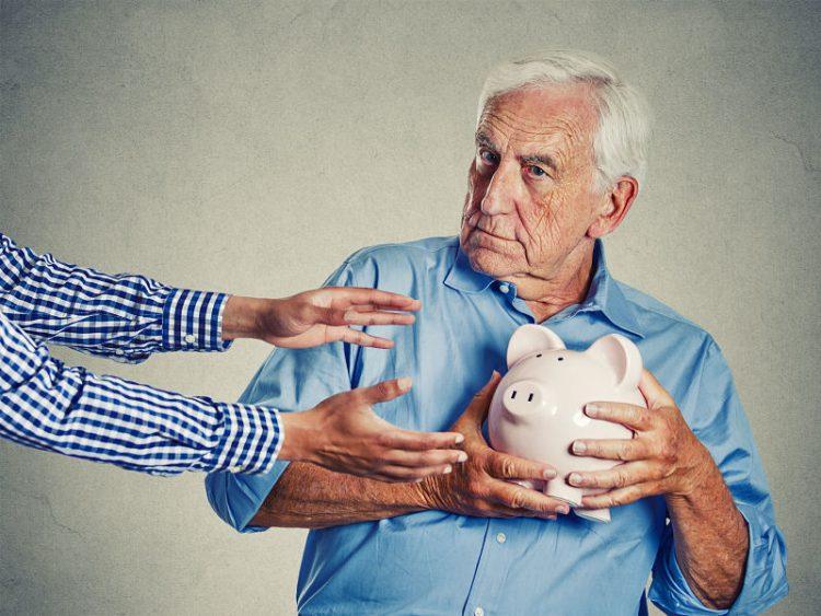loseup portrait senior man protecting a piggy bank