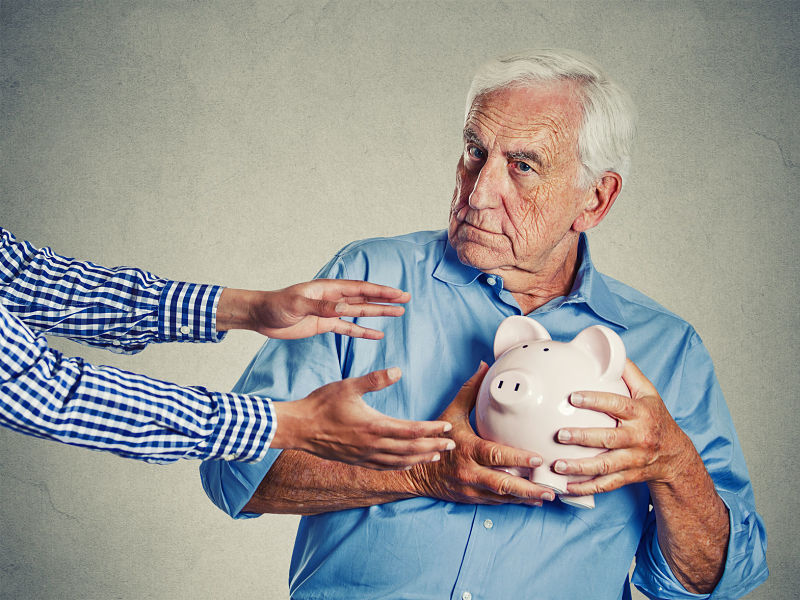 loseup portrait senior man protecting a piggy bank