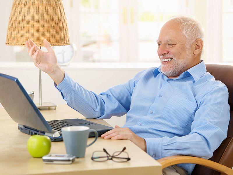 Laughing senior man using laptop computer at home