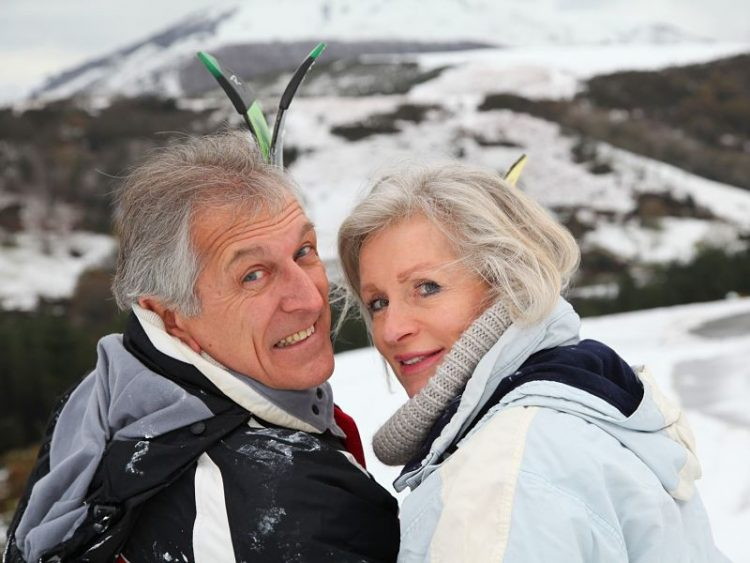 Senior couple with skis, mountain backgroung