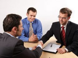 three businessmen sitting at a table negotiating and signing a contract. handskake. mediation concept.