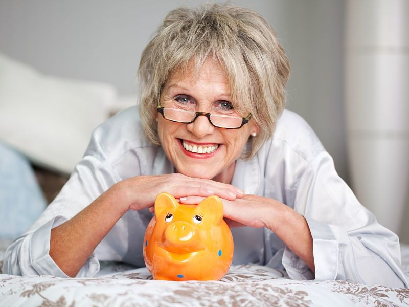 happy senior female lying on bed with piggybank