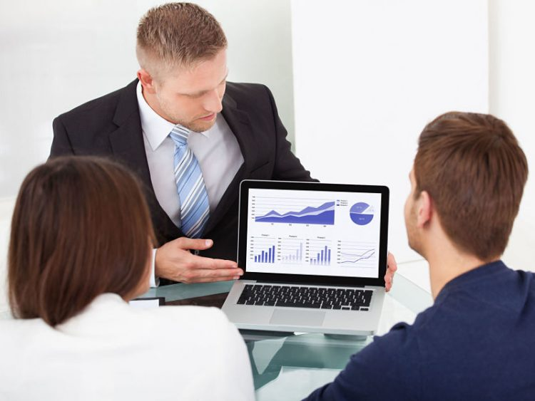 financial advisor explaining investment plan to couple on laptop at office desk