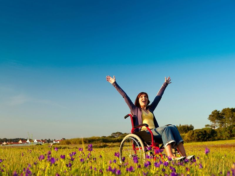 Young woman on a wheelchair over a green meadow