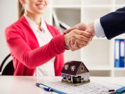 female homebuyer shakes hand with real estate agent in office