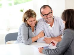 boomer couple signing contract with financial planner