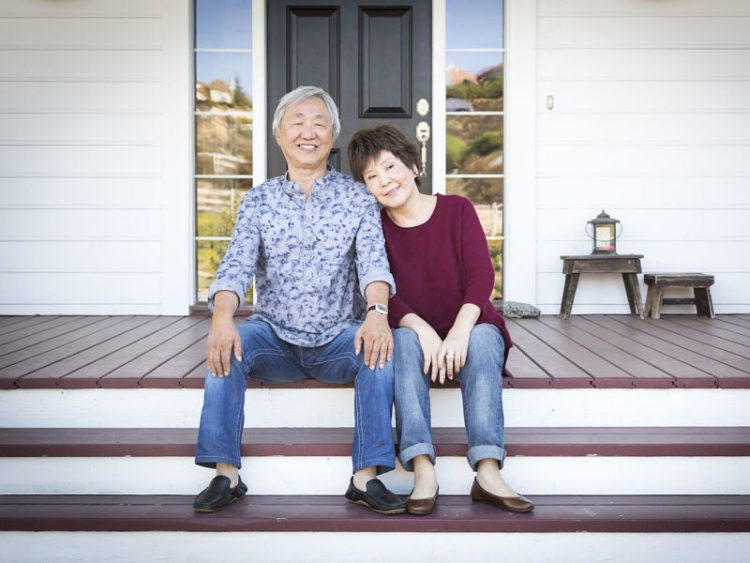 tractive happy senior chinese couple sitting on the front steps of their house.