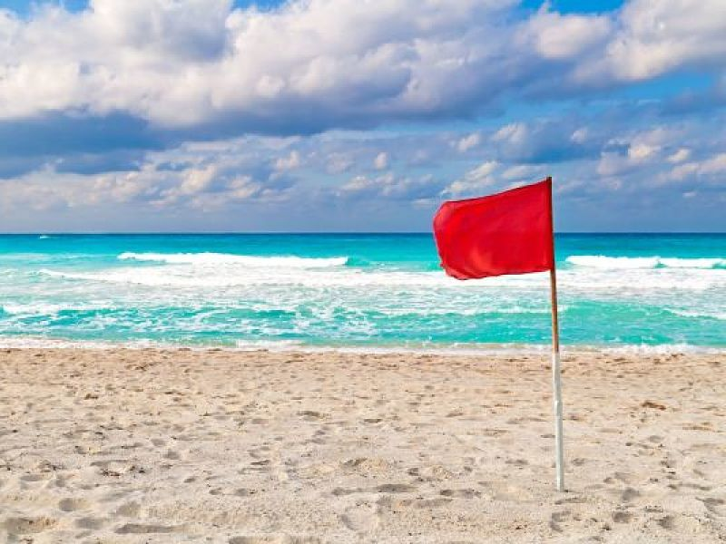 red warning flag on a stormy beach