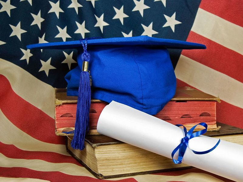 US flag, blue graduation cap and diploma on old books