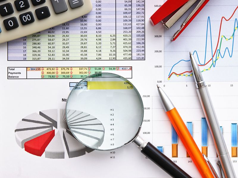 pen, magnifying glass and financial graphs