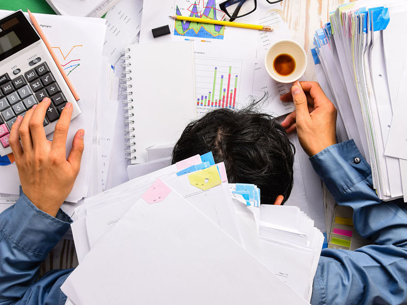 businessman heavy workload sleep at office desk with finance sheet calculator and coffee.