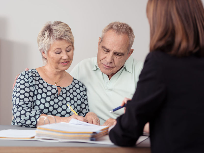middle aged couple discussing something on a document with a female advisor at the table
