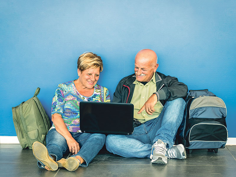 Mature couple travelling with backpacks and laptop