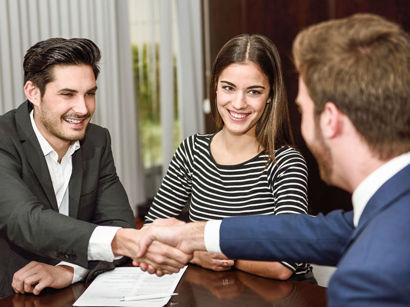 smiling young couple shaking hands with investment advisor