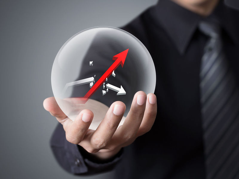 38862292 - businessman holds crystal ball with rising red graph and broken white graph
