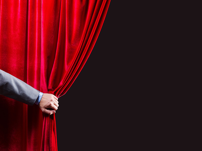 man opening curtain to reveal something