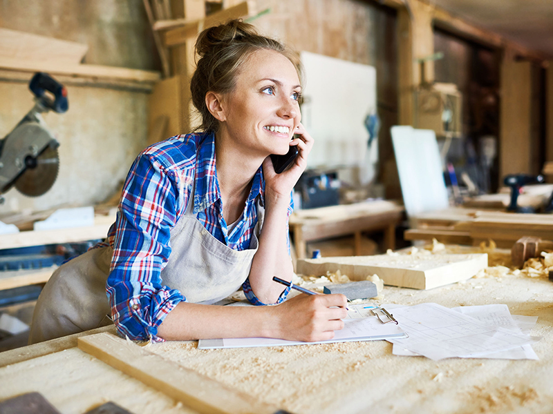 Cheerful young carpenter discussing order details with her customer on smartphone and taking necessary notes, interior of spacious workshop on background