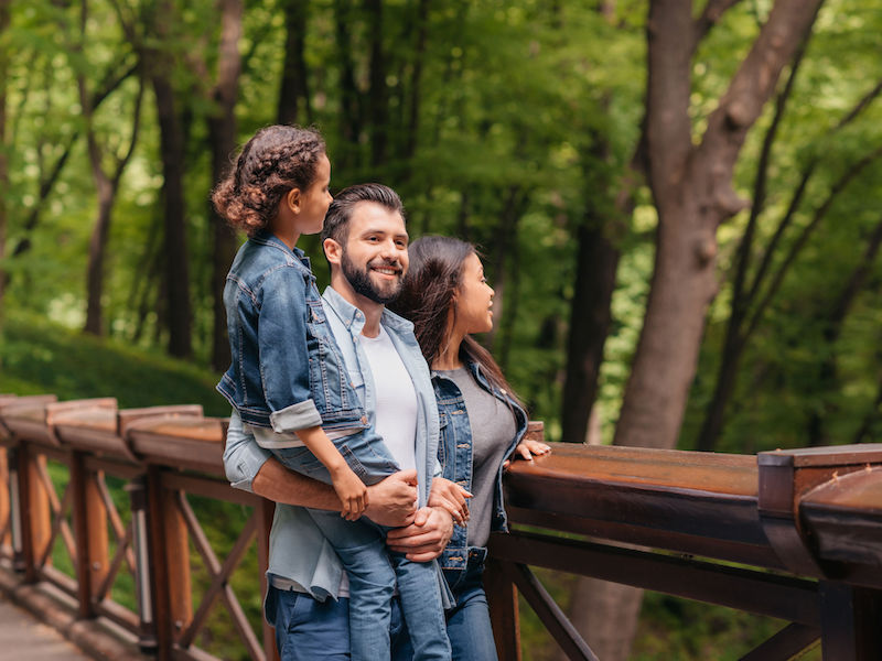 Young happy interracial family standing on wooden bridge, while father holding his daughter in arms