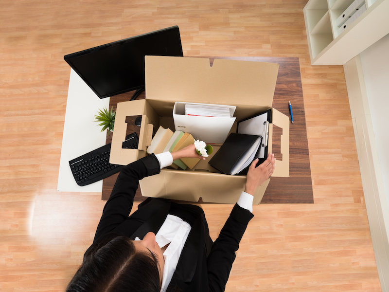 High Angle View Of Businesswoman Packing Personal Belonging In Box