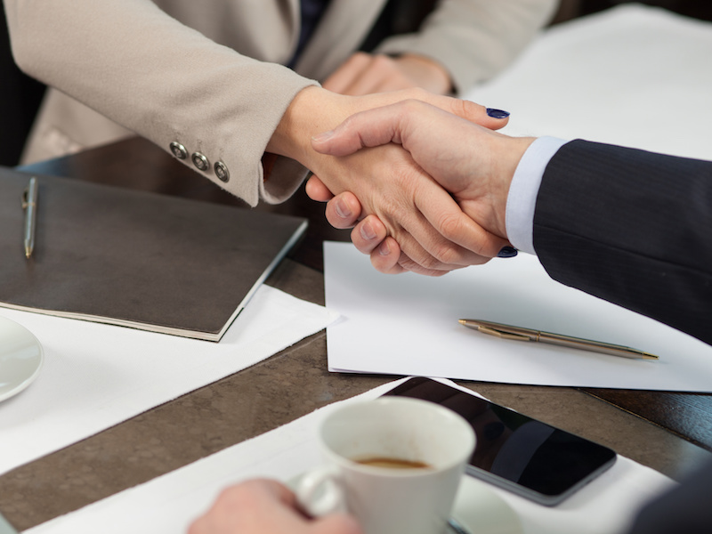We made a deal. Close up of arms of successful two business partners shaking hands. They are sitting at the table near documents in cafe. The businessman and woman are drinking coffee