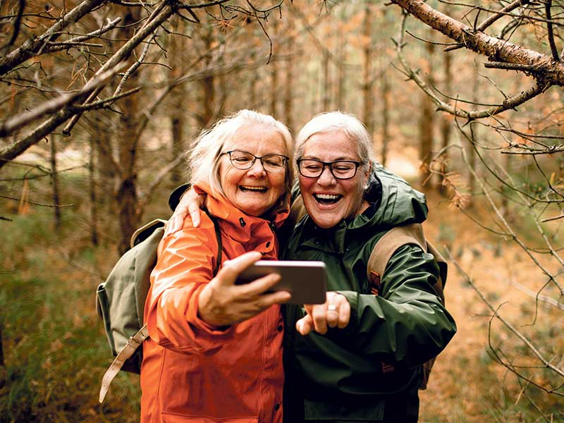 Two senior ladies hiking in the woods