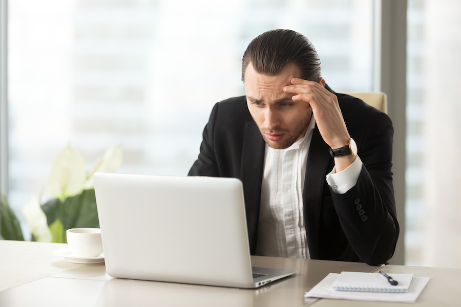 Upset confused businessman looking at laptop screen at workplace in modern office. Stressed young CEO at work desk looking at computer in disbelief about failing report statistics, bad mistake made.