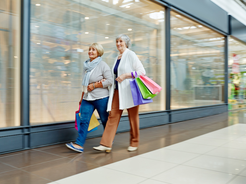Two shopaholics carrying paperbags while walking along shop window