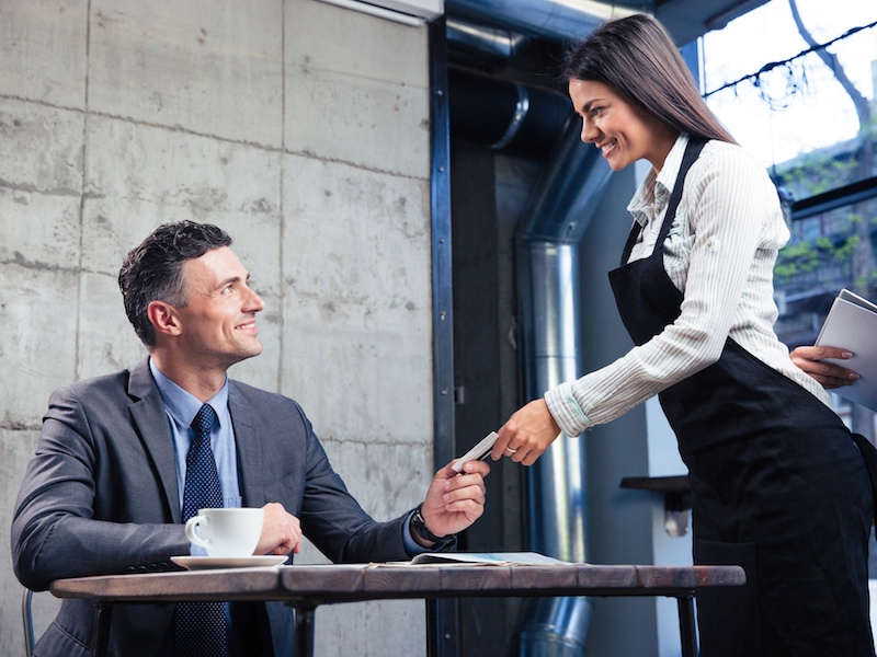 Happy man giving bank card to smiling female waiter in restaurant