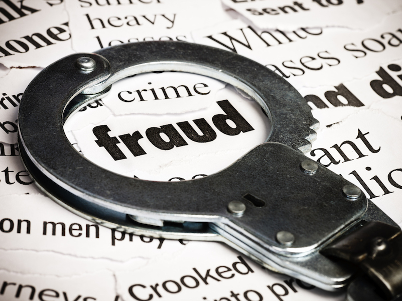 Metal handcuffs placed over the word fraud