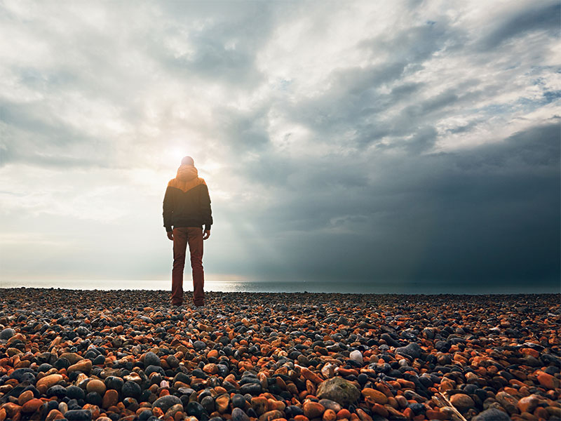 Man on beach looking at the horizon,