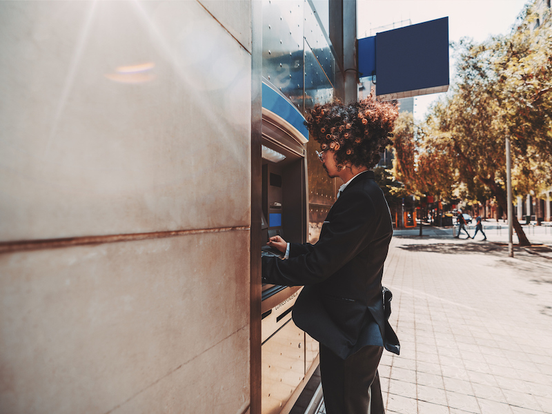 A side view of a curly fancy businessman in a formal suit using an outdoor cash dispenser to withdraw money from his account, with a copy space place on the left for your text or logo (A side view of a curly fancy businessman in a formal suit using an