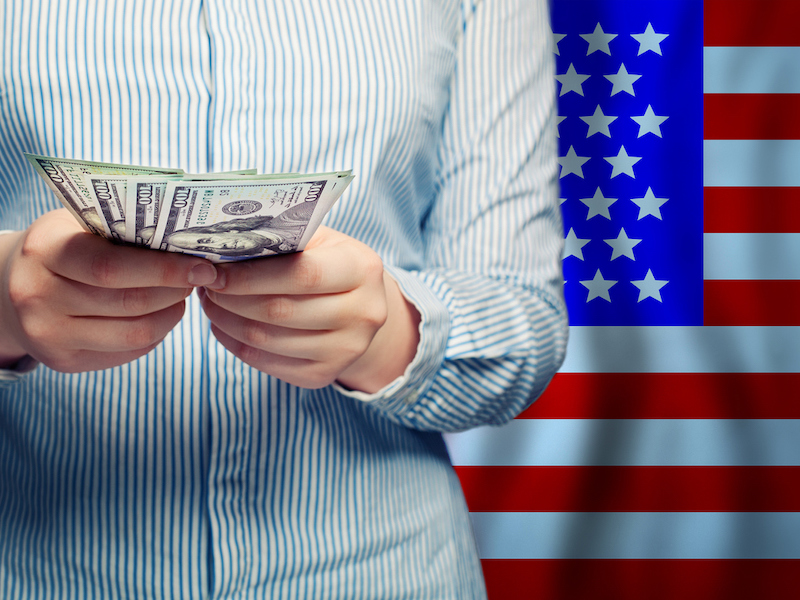 Hands counts money on American flag background