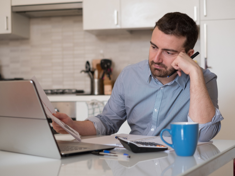 Frustrated man calculating bills and tax expenses