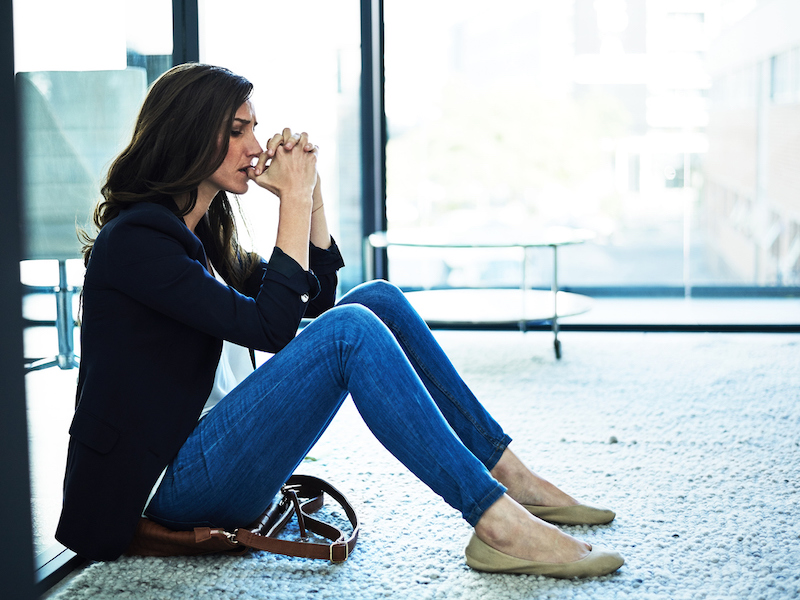 Shot of a stressed businesswoman sitting on the floor outside the boardroom
